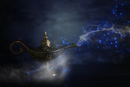 Image of magical mysterious aladdin lamp with glitter sparkle smoke over black background. Lamp of wishes 写真素材