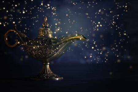 Image of magical mysterious aladdin lamp with glowing glitter lights over black background. Lamp of wishes Stock Photo