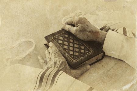 Old Jewish man hands holding a Prayer book, praying, next to tallit. Jewish traditional symbols. Rosh hashanah (jewish New Year holiday), Shabbat and Yom kippur concept