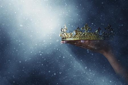 imagen misteriosa y mágica de la mano de la mujer sosteniendo una corona de oro sobre fondo negro gótico. Concepto de época medieval Foto de archivo