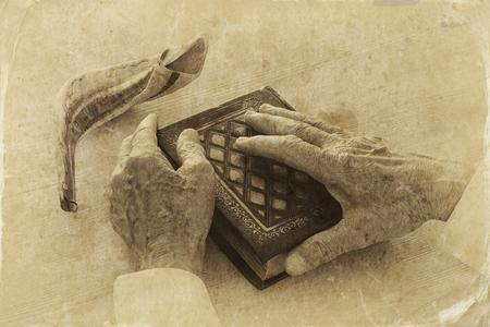 Old Jewish man hands holding a Prayer book, praying, next to shofar (horn). Jewish traditional symbols. Rosh hashanah (jewish New Year holiday) and Yom kippur concept Stock Photo