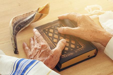Old Jewish man hands holding a Prayer book, praying, next to tallit and shofar (horn). Jewish traditional symbols. Rosh hashanah (jewish New Year holiday) and Yom kippur concept.