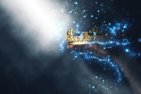 geheimnisvolles und magisches Bild der Hand der Frau, die eine goldene Krone über gotischem schwarzem Hintergrund hält. Mittelalterliches Konzept