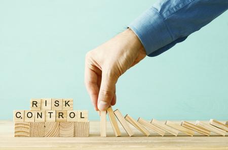 immagine della mano maschile che ferma l'effetto domino. concetto esecutivo e di controllo del rischio