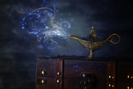 Image of magical mysterious aladdin lamp with glitter sparkle smoke over black background. Lamp of wishes Archivio Fotografico