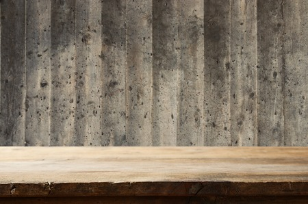 Empty table in front of exposed concrete textured wall background. For product display montage Reklamní fotografie