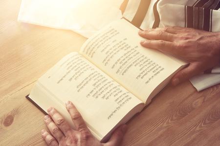Jewish man hands holding a Prayer book, praying, next to tallit. Jewish traditional symbols. Rosh hashanah (jewish New Year holiday), Shabbat and Yom kippur concept Stock Photo