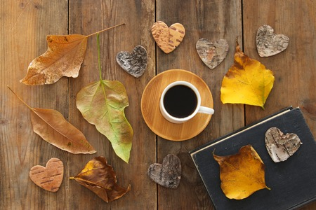 top view image of coffee cup over wooden , dry autumn leaves and stack of book Foto de archivo