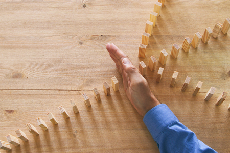 image of male hand stopping the domino effect. retro style image executive and risk control concept