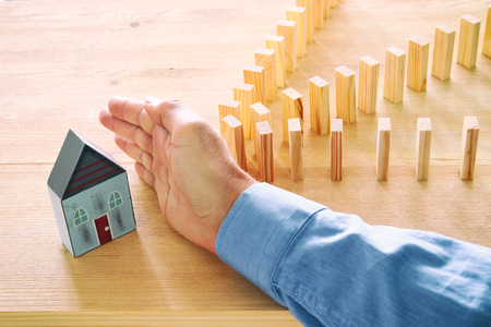 concept image of real estate insurance and protection. man hands blocking the domino effect, saving a small house