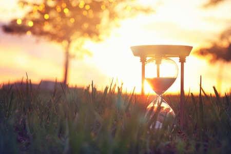 Hourglass in the grass time during sunset. vintage style