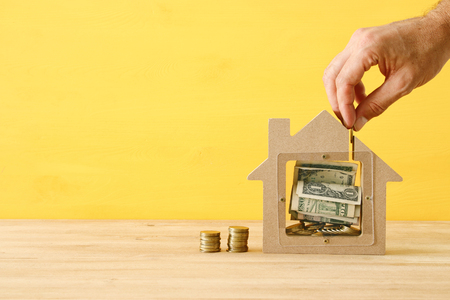 Mortgage concept. Model of a wooden house with financial savings. house purchase and expenses