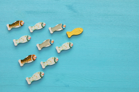Leadership concept with swimming fish on wooden background. One leader leads others Stock Photo