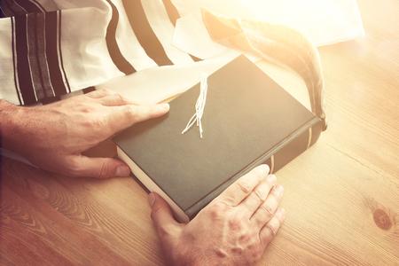 Jewish man hands holding a Prayer book, praying, next to tallit. Jewish traditional symbols. Rosh hashanah (jewish New Year holiday), Shabbat and Yom kippur concept