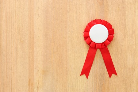 red award ribbon over wooden table Stock Photo