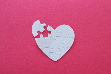 Top view image of paper white heart puzzle with missing piece over pink background. Health care, donate, world heart day and world health day concept
