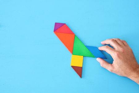 rocket made from tangram puzzle on blue pastel wooden background Stock Photo