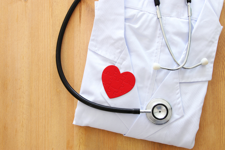 Image of stethoscope and doctor coat over wooden desk. Medical concept