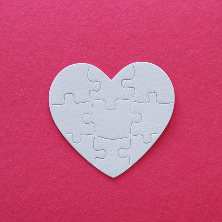 Top view image of paper white heart puzzle over pink background. Health care, donate, world heart day and world health day concept