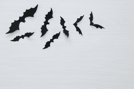 Halloween holiday concept. Black bats over white background. Top view, flat lay