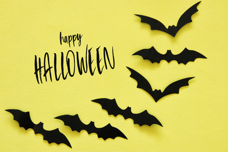 Halloween holiday concept. Black bats over yellow background. Top view, flat lay Stock Photo