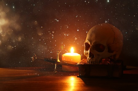 Human skull, old book, sword and burning candle over old wooden table and dark background