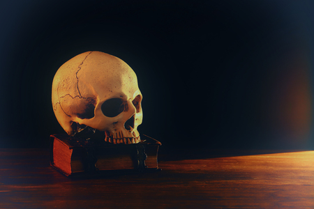 Human skull and old book over old wooden table and dark background Banque d'images