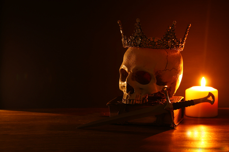 Human skull, old book, sword, crown and burning candle over old wooden table and darl background