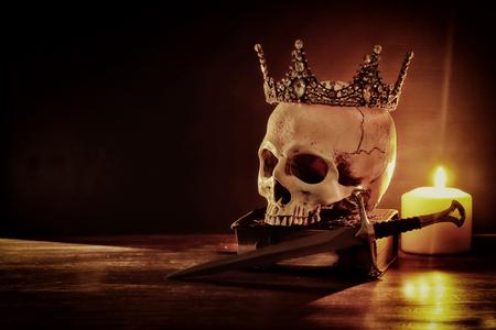 Menschlicher Schädel, altes Buch, Schwert, Krone und brennende Kerze über altem Holztisch und dunklem Hintergrund
