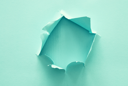 Mint pastel color background with hole in the paper. Copy space