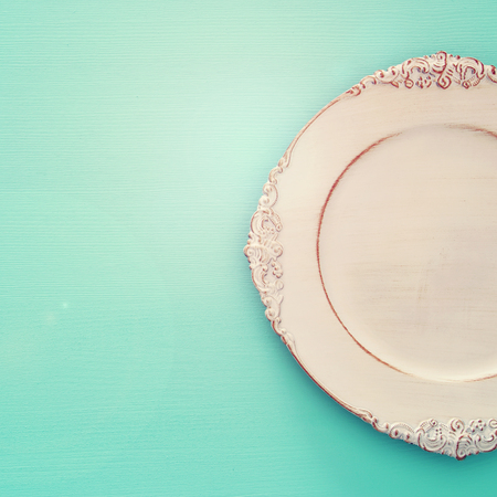 Top view of vintage white empty plate over blue mint wooden background. Flat lay.