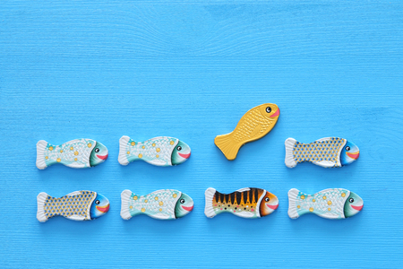 different fish swimming opposite way of identical ones. Courage and success concept Stock Photo
