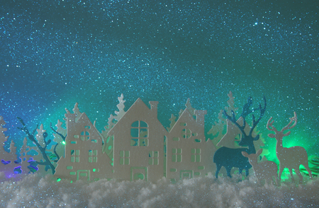 Magical Christmas paper cut winter background landscape with houses, trees, deer and snow in front of northern lights background