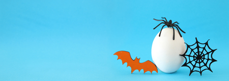 minimal and funny Halloween holiday concept. White egg with spiderweb, bat and spider on top Stock Photo