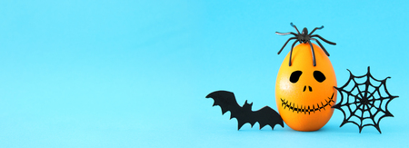minimal and funny Halloween holiday concept. Orange egg with scary cute face, spiderweb, bat and spider on top. Banner