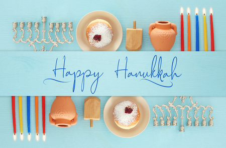 Top view image of jewish holiday Hanukkah background with traditional spinnig top, menorah (traditional candelabra) and burning candles Archivio Fotografico