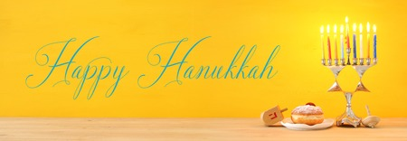 Banner of jewish holiday Hanukkah background with traditional spinnig top, menorah (traditional candelabra) and burning candles. Archivio Fotografico
