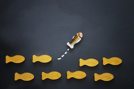 Different fish swimming opposite way of identical ones. Courage and success concept. Blackboard background