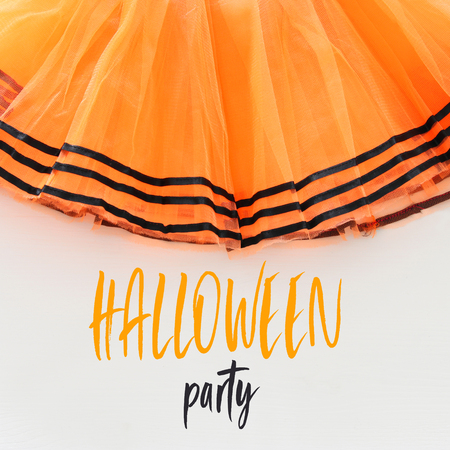 Halloween holiday minimal top view image of orange tulle skirt costume over white wooden background. Text HALLOWEEN PARTY