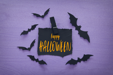 Halloween holiday minimal top view image of letter with text HAPPY HALLOWEEN over wooden purple background. Card and invitation concept Banque d'images