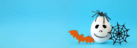 Minimal and funny Halloween holiday concept. White egg with scary cute face, spiderweb, bat and spider on top. Banner