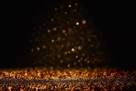 Glitter vintage lights background. Black and gold. De-focused. Stock Photo