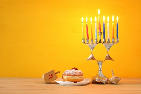 Image of Jewish holiday Hanukkah background with traditional spinning top, menorah (traditional candelabra) and burning candles
