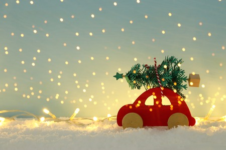Red wooden car carrying a christmas tree over snow in front of blue background and golden garland lights