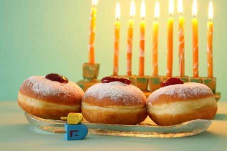Image of Jewish holiday Hanukkah background with doughnuts and menorah (traditional candelabra) Stock Photo