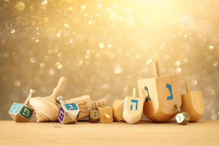 Banner of Jewish holiday Hanukkah with wooden dreidels (spinning top) over glitter shiny background Stock Photo
