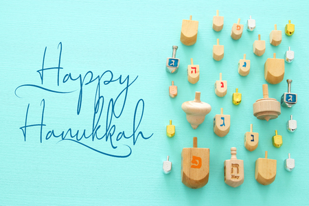 Image of jewish holiday Hanukkah with wooden dreidels colection (spinning top) over mint background Stock Photo
