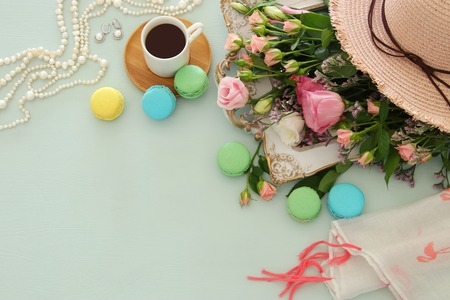 plate of macaroons over wooden table coffee and flowers