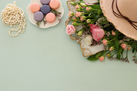 Plate of macaroons over wooden table and flowers Foto de archivo