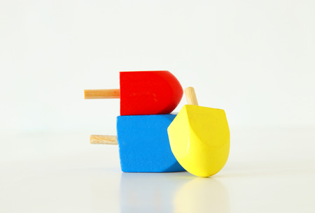 Image of Jewish holiday Hanukkah with wooden dreidels collection (spinning top) over white background